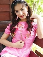 View the wonderful Annita Sang as she sits on a wooden porch in her pink top