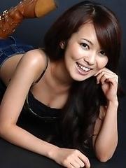 Flirtatious asian babe in a blue jean mini skirt and boots